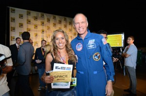 Photo by ©WBEI. Chief Test Pilot/former NASA Astronaut Richard Searfoss (right) and space flight winner Mercedes Becerra of Paso Robles.